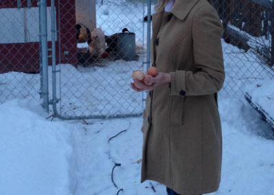 Melinda collecting eggs from our chickens!