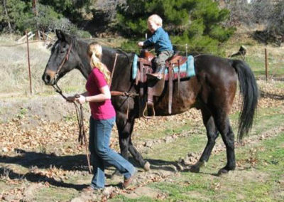 Melinda leading son on her horse.
