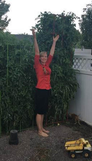 Melinda next to Russel's tomato plant, it grew 3 more feet after this picture!