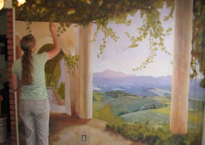 Melinda painting a mural.
